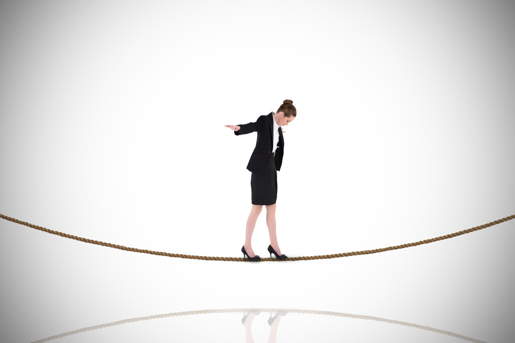 Businesswoman performing a balancing act on tightrope against wh